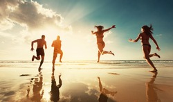 Four friends are having fun at sunset sea beach