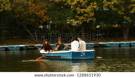Four friends (2 boys and 2 girls) taking a boat trip on Herastrau Lake in Romania in a beautiful day. Other boats are in the harbour, the colors are amazing, a boy is paddling and two guys are in love #1288651930