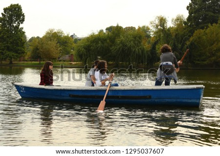 Four friends (2 boys and 2 girls) taking a boat trip on Herastrau Lake in Romania in a beautiful day. Other boats are in the harbour, the colors are amazing, a boy is paddling and two guys are in love #1295037607