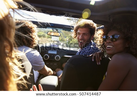 Shutterstock Four friends driving in an open top car, rear passenger POV