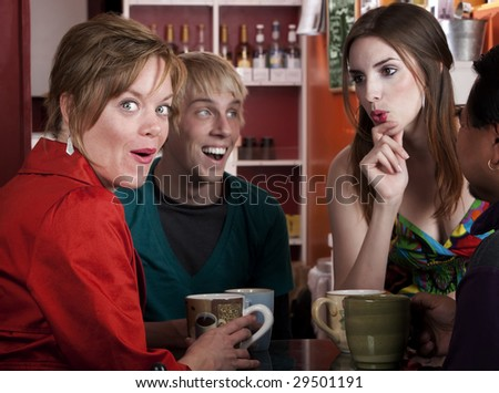 Four friends having an animated discussion in a coffee house