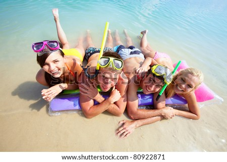 Four friends in scubas lying on sand by water