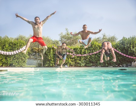 Four friends jumping into a swimming pool - Happy people having fun and diving into water - Tourists on summertime vacation in a tropical resort