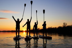 Four friends on stand up paddle board (SUP) on a flat quiet winter river at sunset raising his paddles up