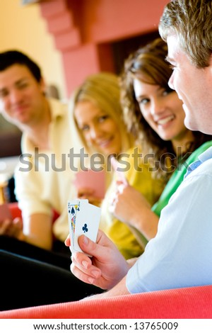 Four friends playing poker at home