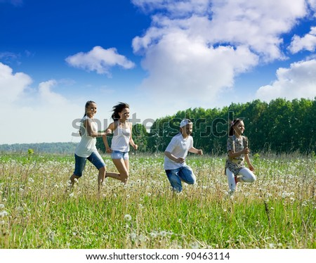 Four friends running at meadow in summer