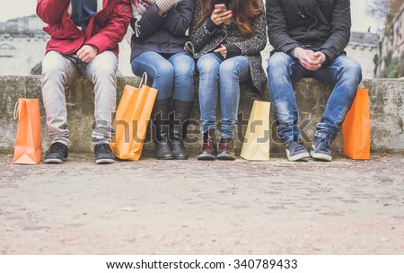 Four friends sitting on a wall and chatting after buying presents - people with shopping bags