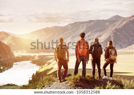 Four friends stands on view point and looking at sunset mountains and river. Adventures travel concept with space for text Stockfoto ©