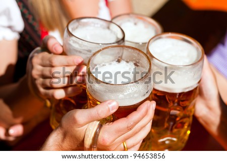 Four friends with a fresh beer in a Beer garden close-up on beer stein