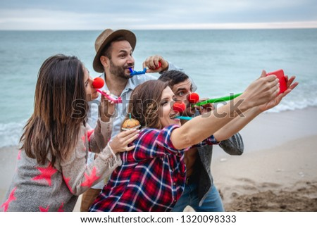 Four friends with red noses take a selfie and celebrate a birthday on the beach