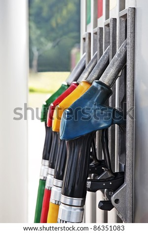 Four gas pump nozzles on the petrol station
