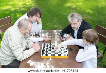 Four generations of men playing chess in the garden - stock photo