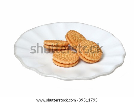 Four generic sandwich cookies on a white plate. Isolated.