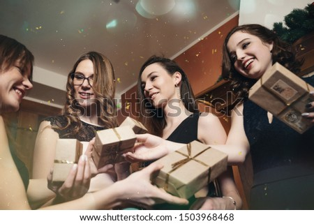 Four girlfriends celebrate New Year or Christmas by the fireplace. Laugh and give gifts to each other #1503968468
