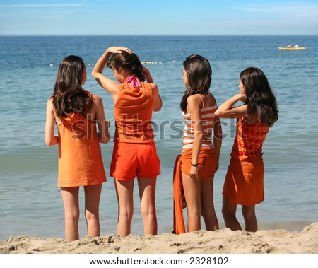 Four girls in orange clothes standing on the beach