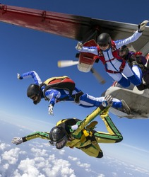 Four girls parachutists jump out of an airplane.
