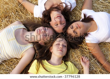 Four girls resting on hay