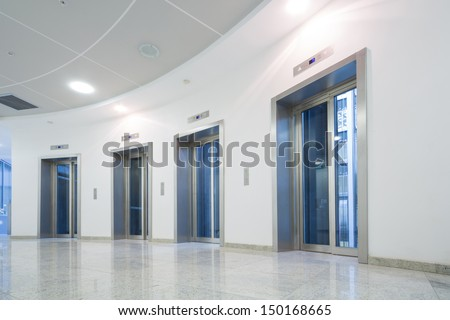 Four glass elevator door in the business building - stock photo