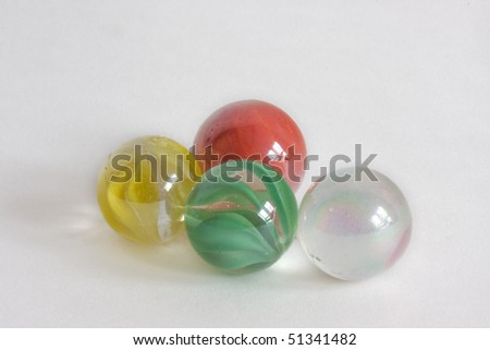 Four glass marbles, transparent, green, yellow and red.