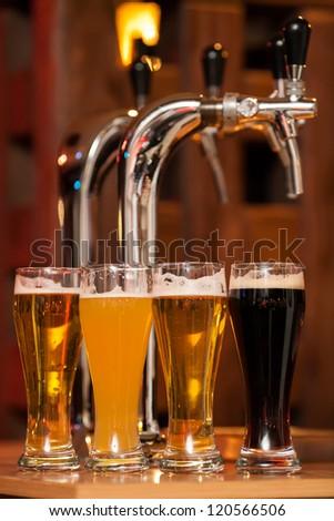 Four glasses of beer against beer tap