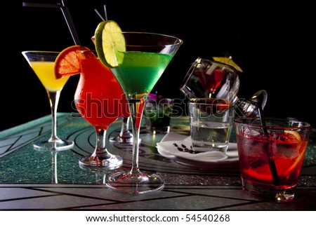 Four glasses of colorful cocktails in dark