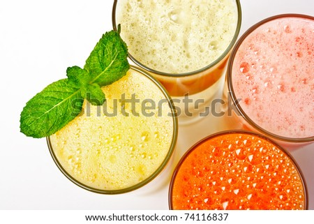 Four  glasses of different fresh juice,  over white, close up from above (orange carrot apple grapefruit)