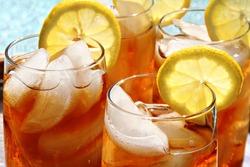 Four glasses of lemon ice tea, outside by the pool.