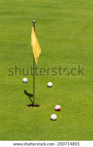 Four golf balls near yellow checkered flag.