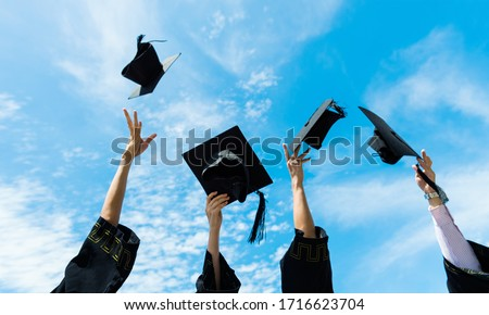 Four graduates throwing graduation hats in the air.