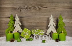 Four green burning christmas candles with presents and trees on wooden background for a gift card.