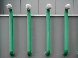 Four green fire hydrants on the gray wall