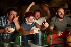 Four guys cheering in front of TV while watching american football game