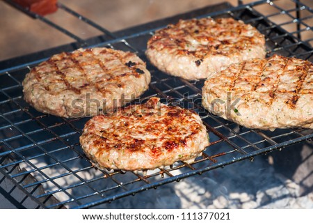 Four Hamburgers on Barbeque Grill