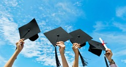 Four hands holding graduation hats on background of blue sky.