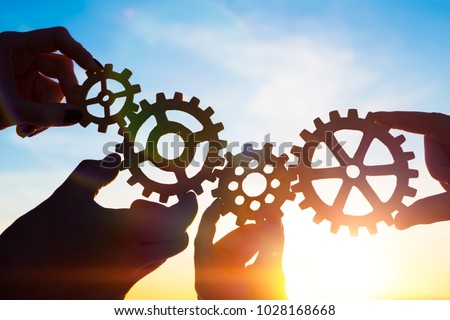 Photo of  Four hands of businessmen collect gear from the gears of the details of puzzles. against the background of sunlight. The concept of a business idea. Teamwork. strategy. cooperation