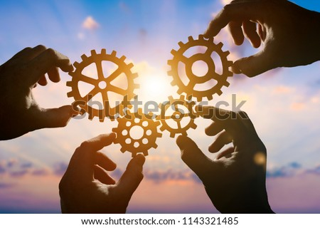 Four hands of businessmen collect gear from the gears of the details of puzzles. against the backdrop of dramatic sunlight. The concept of a business idea. Teamwork, strategy, cooperation, creativity #1143321485