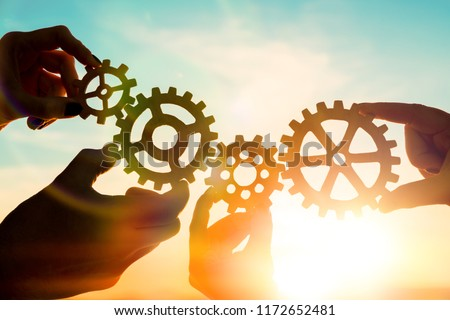 Four hands of businessmen collect gear from the gears of the details of puzzles. against the sunset. The concept of a business idea. Teamwork, strategy, cooperation, innovation. #1172652481