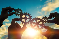 Four hands of businessmen connect gears to a puzzle on a background of sunset. Business concept idea, partnership, cooperation, teamwork, community, creative