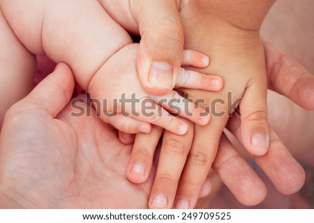 Four hands of the family. The concept of love, friendship, happiness in the family. Tinted image.Toned image.