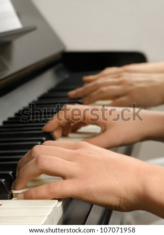 Four hands playing on the piano keys while the teacher gives the student a lesson - stock photo