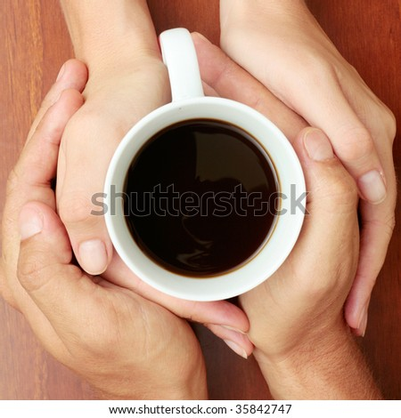 Four hands wrapped around a cup of coffee