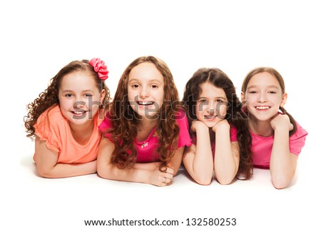Four happy amazing 10 years old girls in pink laying on the floor, isolated on white