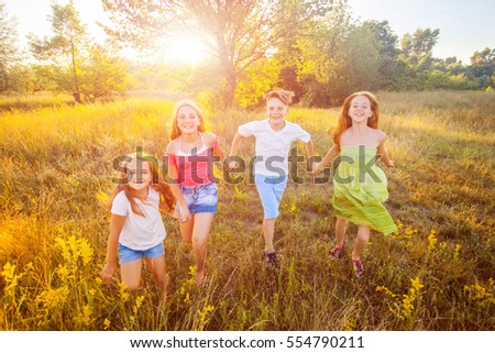 four happy beautiful children running playing moving together in the beautiful summer day. jumping and looking at camera with happiness and toothy smile.   - Shutterstock ID 554790211