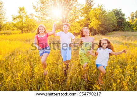 four happy beautiful children running playing moving together in the beautiful summer day. jumping and looking at camera with happiness and toothy smile.   #554790217