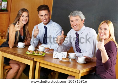 Four happy business people holding their thumbs up in a caf�© - stock photo