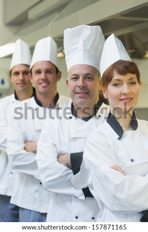 Four happy chefs smiling at the camera wearing uniforms posing in a kitchen