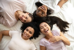 Four happy diverse ethnicity pretty young girls women friends wear pajamas lying in circle on bed laugh look at camera together, sleepover party and multiethnic friendship concept, top view portrait