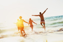 Four happy friends are having fun at sunset sea. Beach holidays concept