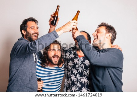 four happy friends celebrating and having fun, laughing out loud and toasting together. friendship, carefree, togetherness concept.