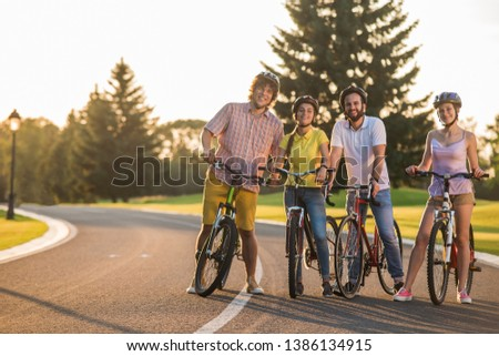 Four happy friends on bikes outdoors. Enjoying summer day together. Cycling, enjoyment and fun.